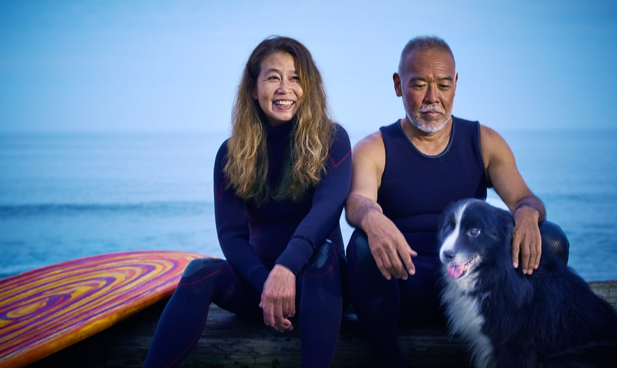 A surfer couple over 50 years old sits with their dog in front of the ocean.