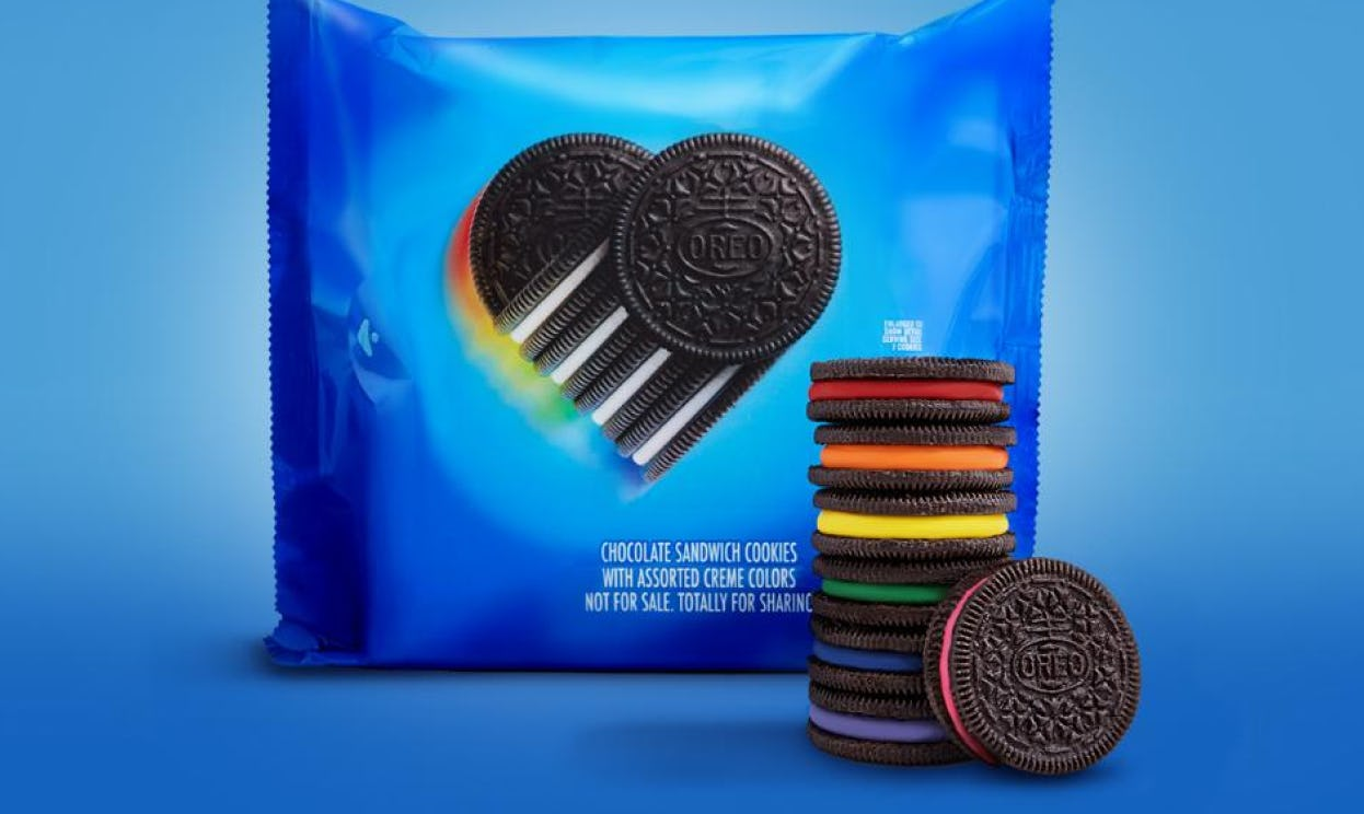 Oreo cookies with rainbow-colored creme centers are stacked in front of Pride-themed Oreo packaging.
