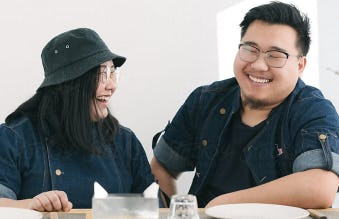 A larger-sized, young Asian couple sitting and smiling together at a table.