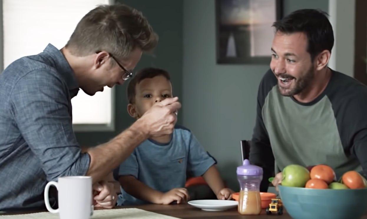 A gay couple enjoys feeding their child at the kitchen table.