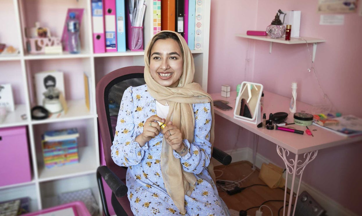Young Muslim woman prepares her makeup in a pink room.