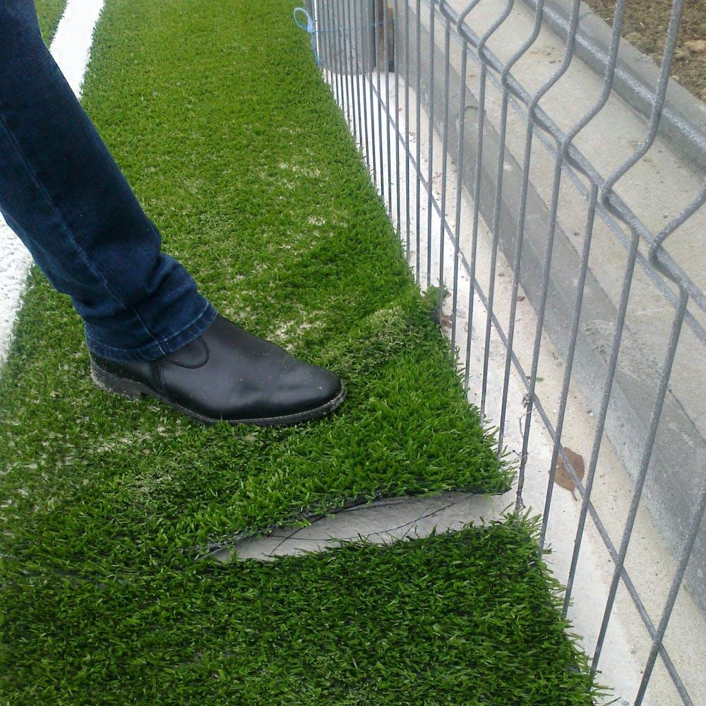 gazon sintetic ridicat de un picior langa gard
