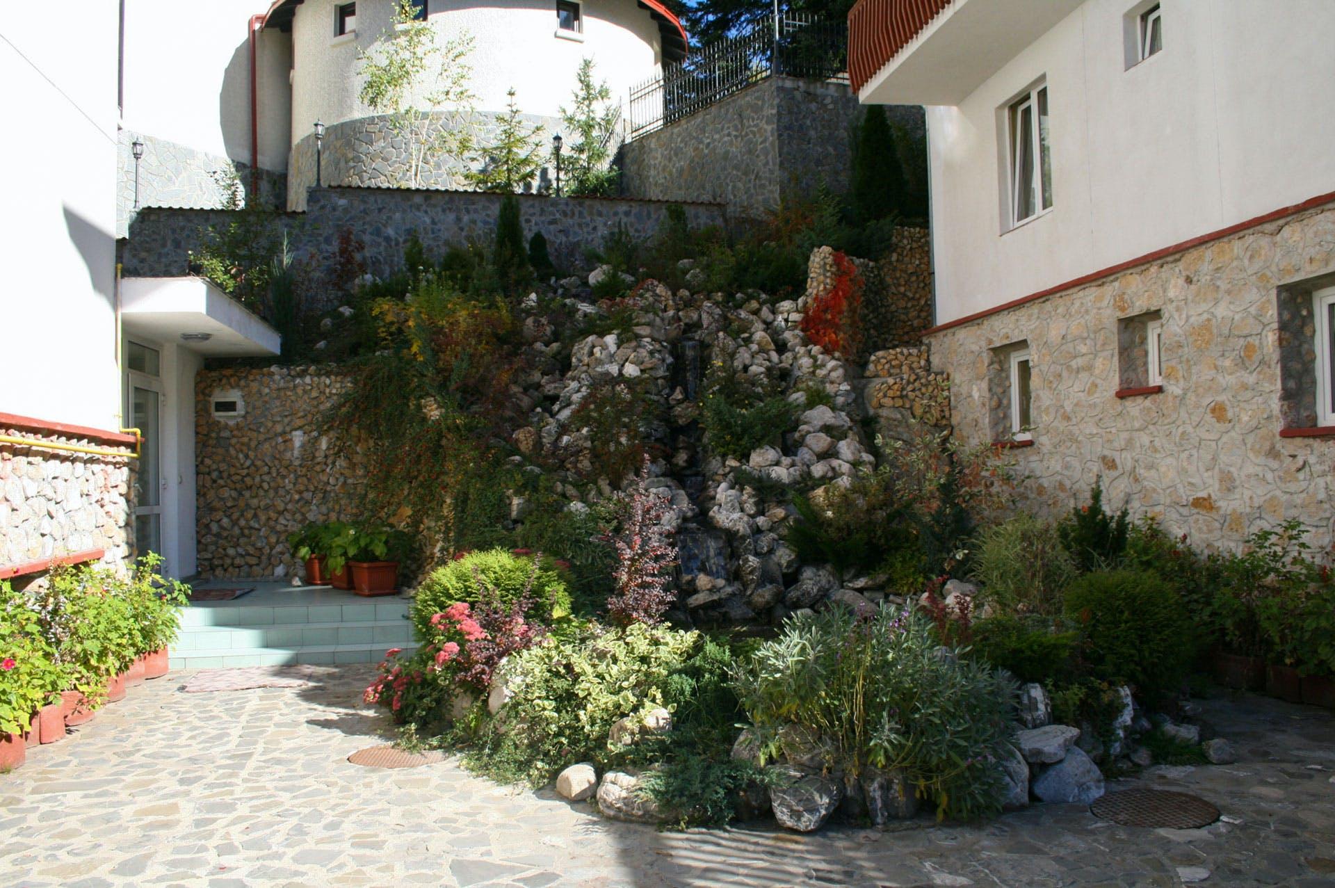 hotel cu cascada ornamentala cu flori plante si rocarie