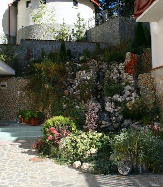cascada si rocarie plina cu plante si flori la un hotel