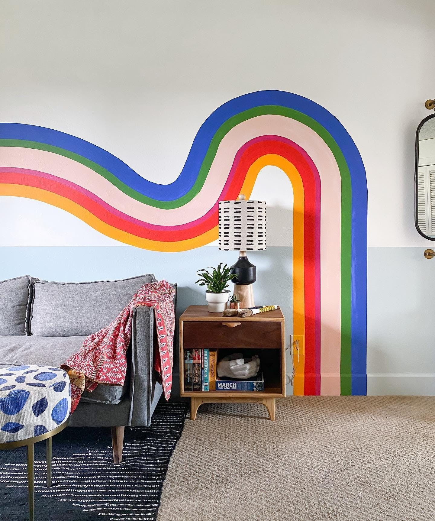colorful curved rainbow mural painted on white walls in living room