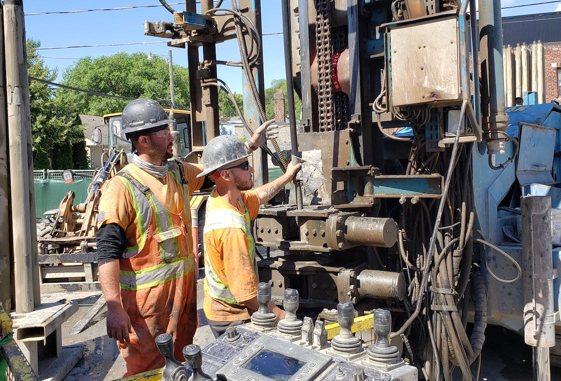 Two workers on site in front of a large drill. One worker is teaching the other.