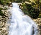 Imagem da cachoeira de Boiçucanga, com queda d'água por pedras e vegetação ao redor.
