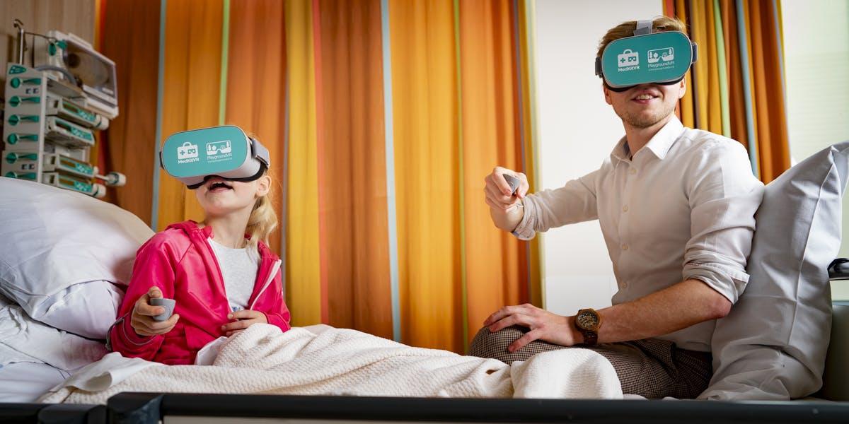 Jason van Eunen en kind spelen PlaygroundVR in ziekenhuisbed
