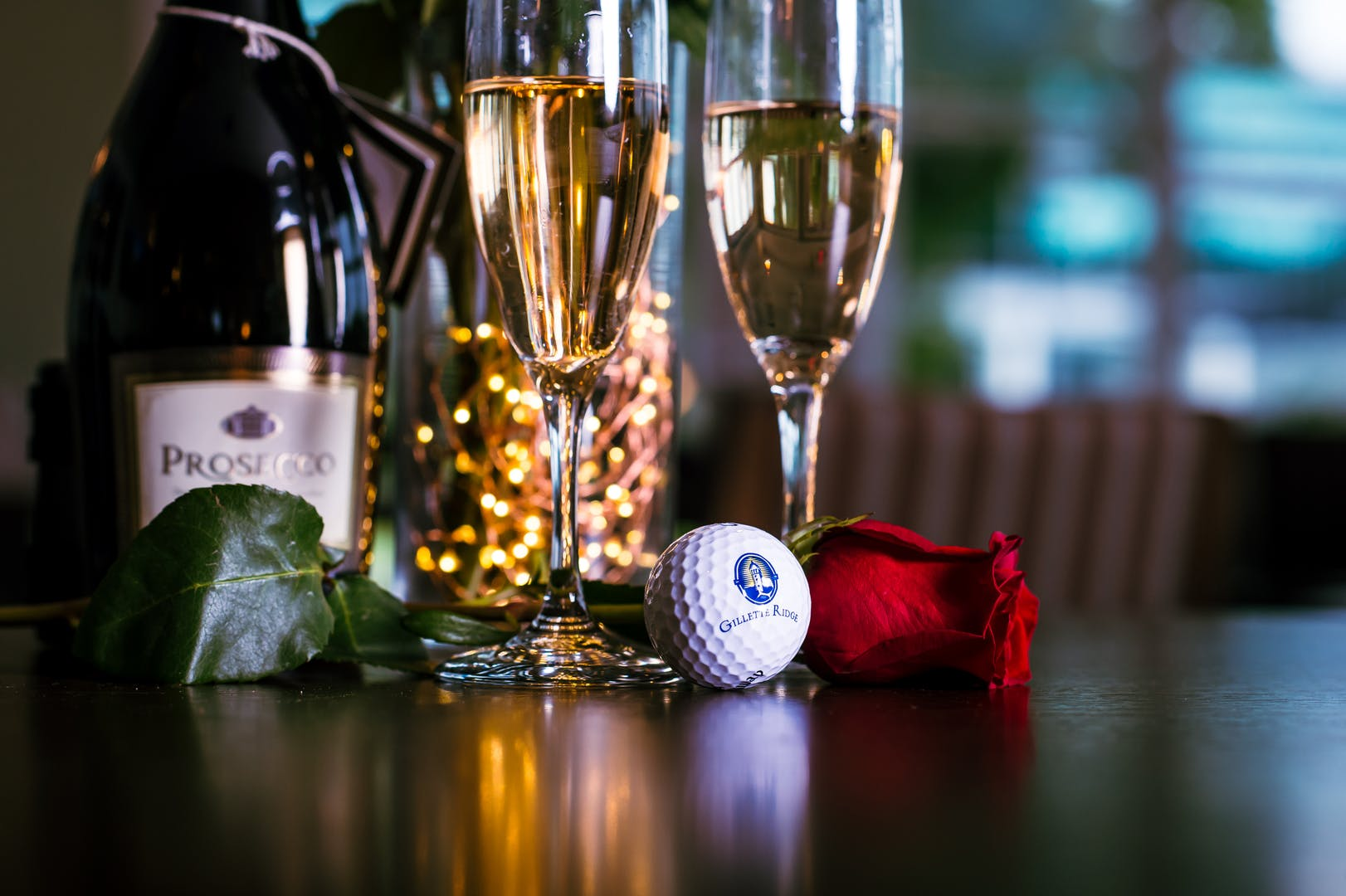 Gillette Ridge logo golf ball, a rose, two flutes of prosecco and a bottle of prosecco arranged on a table.