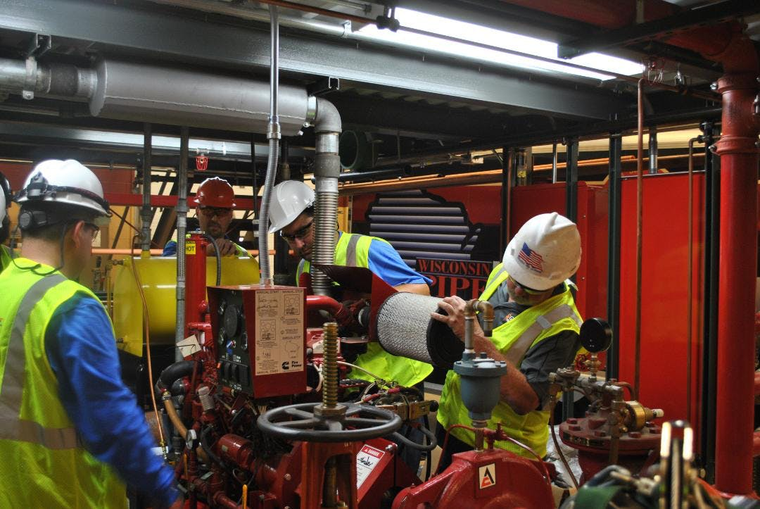 Great Lakes Fire Protection team members working on pipes