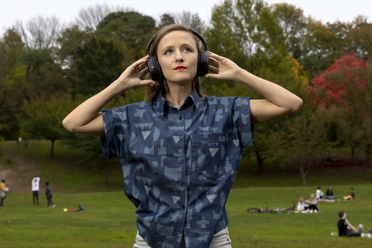 A woman in a blue short-sleeve shirt and wearing headphones puts her hands to her ears while looking toward the sky. She is in a park with trees and people laying on the ground.