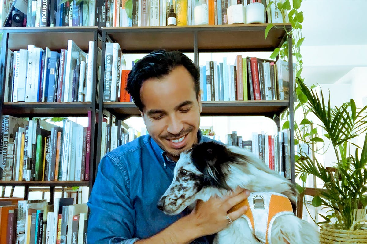 Rodrigo Valenzuela smiles down at a dog in front of a bookcase.