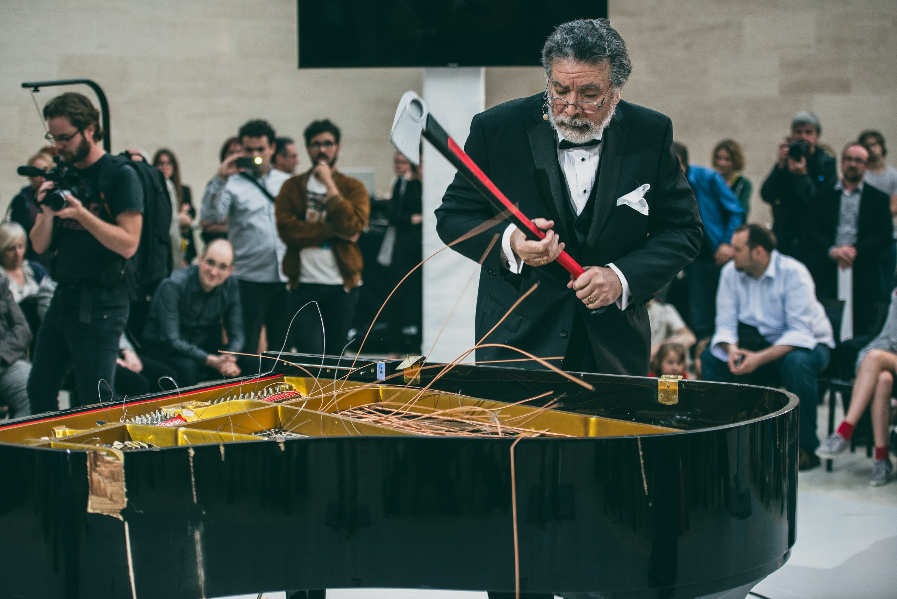 A man in a tuxedo holds an axe in front of a piano with an open top and strings sticking out.
