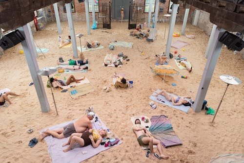 Sunbathers lay out on a man-made beach inside a warehouse