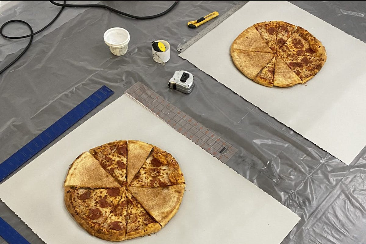 Two pizzas sliced into eighths, and lying on pieces of paper, lying on plastic sheeting.