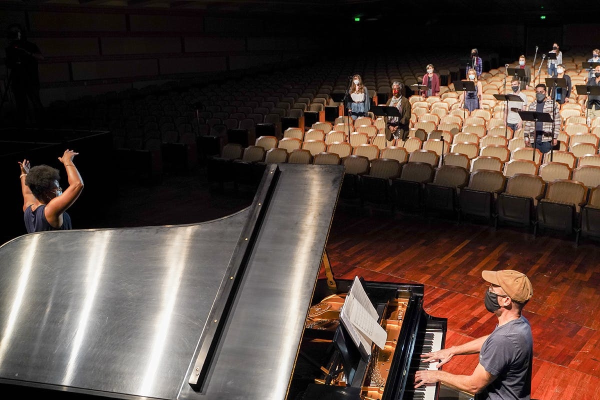 A piano player and performer practice on stage with singers in the backround.