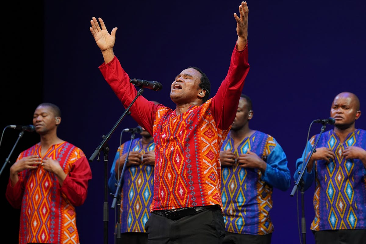 Members of the band Ladysmith Black Mambazo wear either red or blue shirts in traditional patterned designs. The man in the foreground is singing with eyes closed and arms raised.