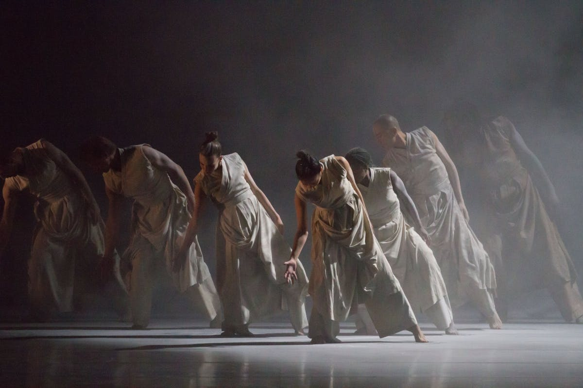A stage full of dancers with a spotlighting and fog.
