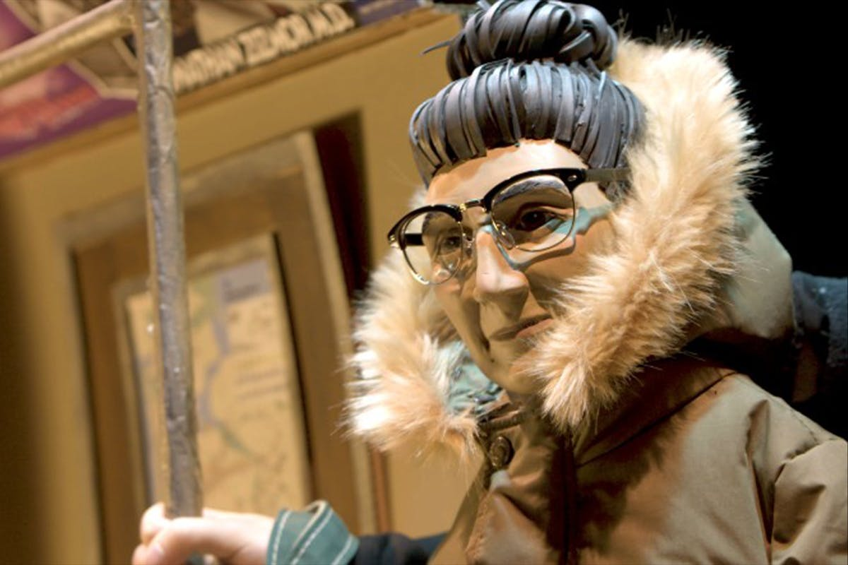 A puppet that looks like an older woman with a fur-collared coat and grey hair tied in a bun and half-rimmed glasses standing on a subway train.