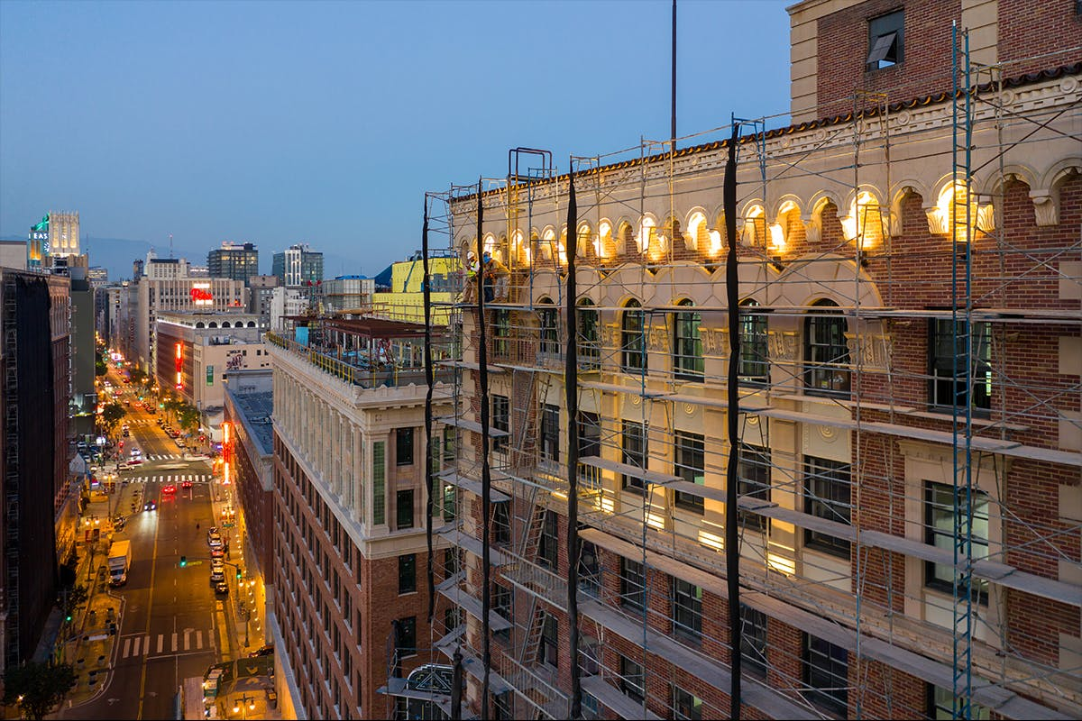 Proper Hotel, designed by Omgivning. Photo by Hunter Kerhart shows scaffolding on a brick building downtown at dusk.