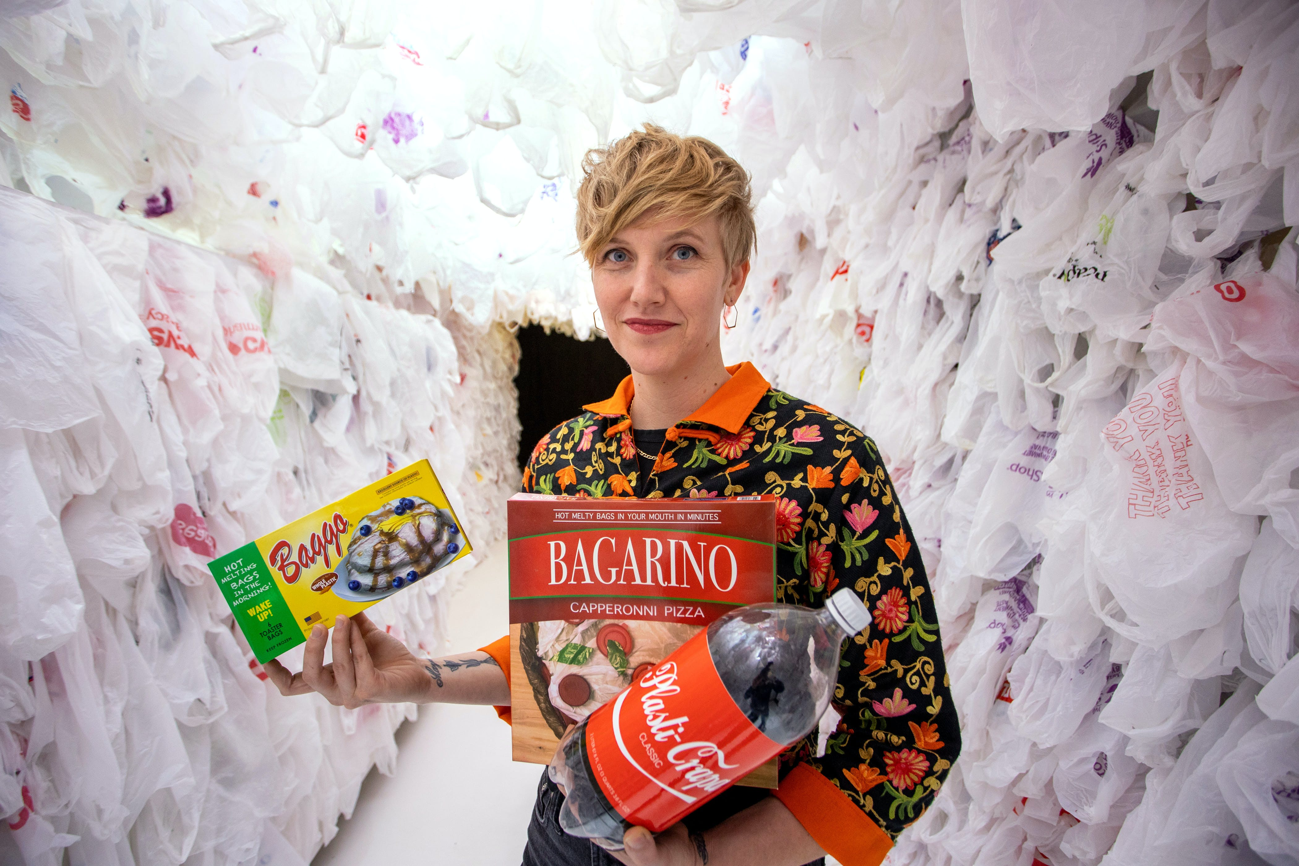 A woman with short blonde hairs stands in a room lined with plastic bags, while holding fake products sold in the Plastic Bag Store.