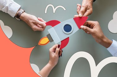Four hands holding a cartoon rocket ship that's taking off