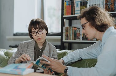 Two people wearing glasses reading in a library.