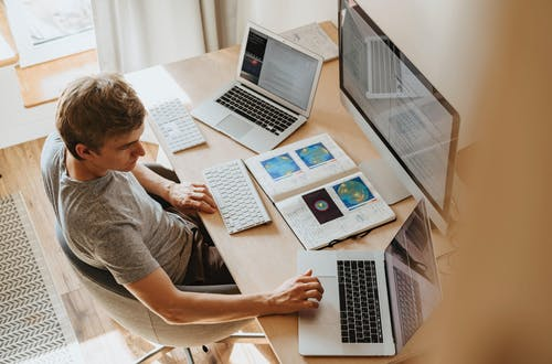 Man with two laptops and a desktop screen working at a desk.