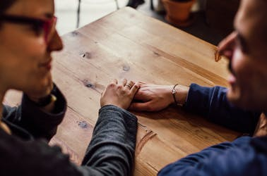 Man and woman talking and holding hands on a wooden table.