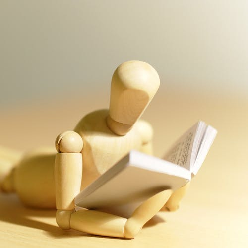 Wooden figurine reading a book.
