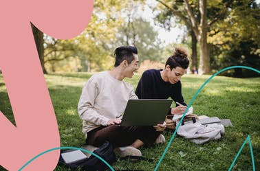 Two people sitting on a grassy field working on a laptop