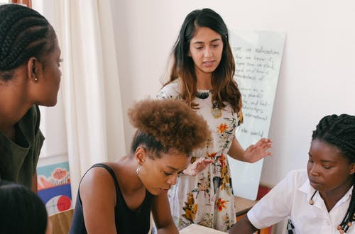 Group of people sitting at a desk, with woman standing in front of a whiteboard.