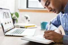 Man in blue and white checked shirt writing in a notebook in front of a laptop.