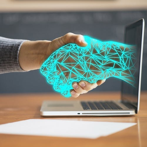 Person shaking hands with a digital arm coming out of a laptop