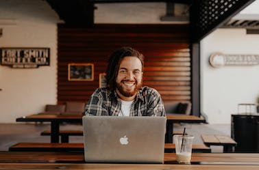 Man sitting behind a laptop smiling (front on view)
