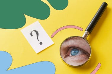 Eye looking into a magnifying glass, next to a question mark on a white piece of paper