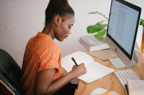 Woman at a desk writing in a notepad in front of a computer.
