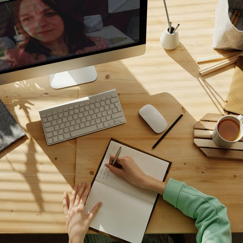 Woman sitting at her desk writing in her notepad, talking to another woman on screen via Zoom.