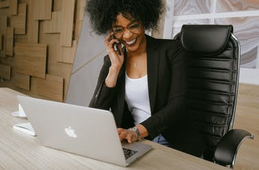 Woman sitting in her office smiling and looking at her laptop