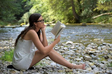 Young woman wearing glasses sitting on stones in front of a lake reading a book.