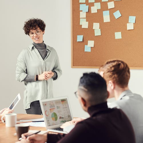 Woman standing up talking to a group of colleagues