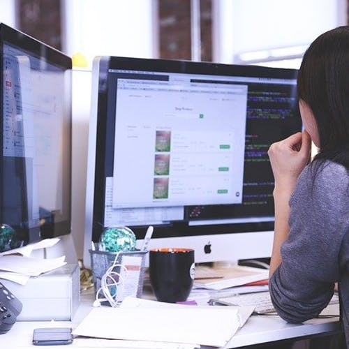 Office worker sitting at her desk looking at two computer screens.