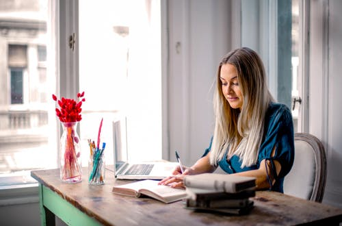 Woman sitting at a laptop writing in a notepad with flowers on her desk.