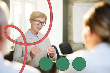 Woman wearing black glasses speaking in a meeting