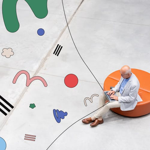 Man working on a laptop surrounded by abstract design