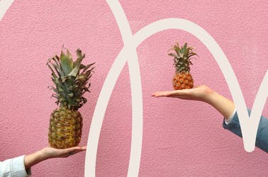 Two people holding different sized pineapples, weighing up their options