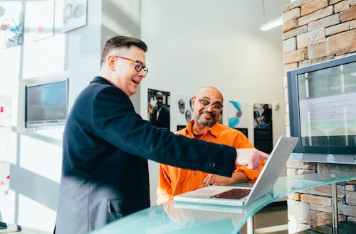 Two men wearing glasses looking at a laptop and pointing at the screen.