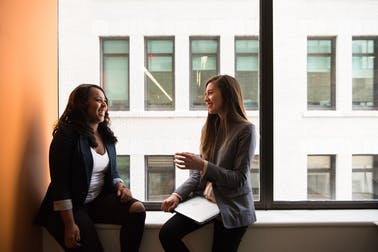 Two business women, talking to one another and smiling, sitting by a window within an inner city office.