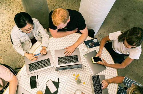 Group of workers sitting at a round table looking at their laptops and phones.