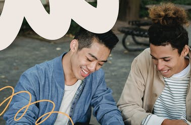 Two male friends sitting on a bench and writing in a notepad